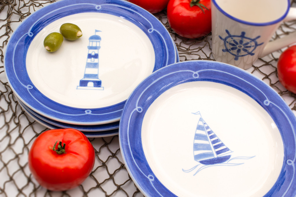 lifestyle of four salad plates with blue rims and assorted blue designs :the lighthouse and sailboat are showing, the other two plates are stacked beneath the lighthouse. the photo is decorated with a couple olives and tomatoes and set on a fishnet background and features one matching mug with a ships wheel icon