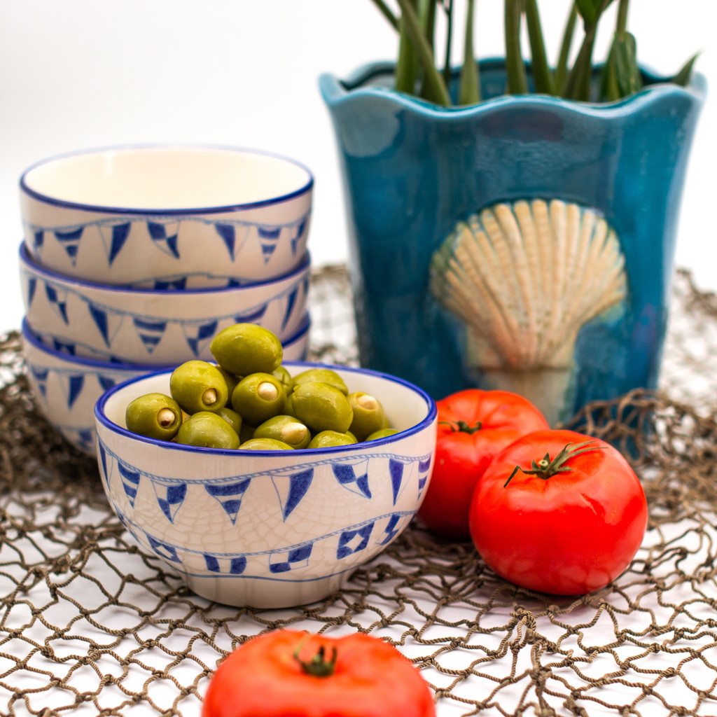 """lifestyle of four bowls with various """"flag language"""" flags arranged on their exteriors. three bowls are stacked and one is in front and filled with olives. the photo is decorated with tomatoes and set on  a fishnet background and features a turquoise seashell planter"""