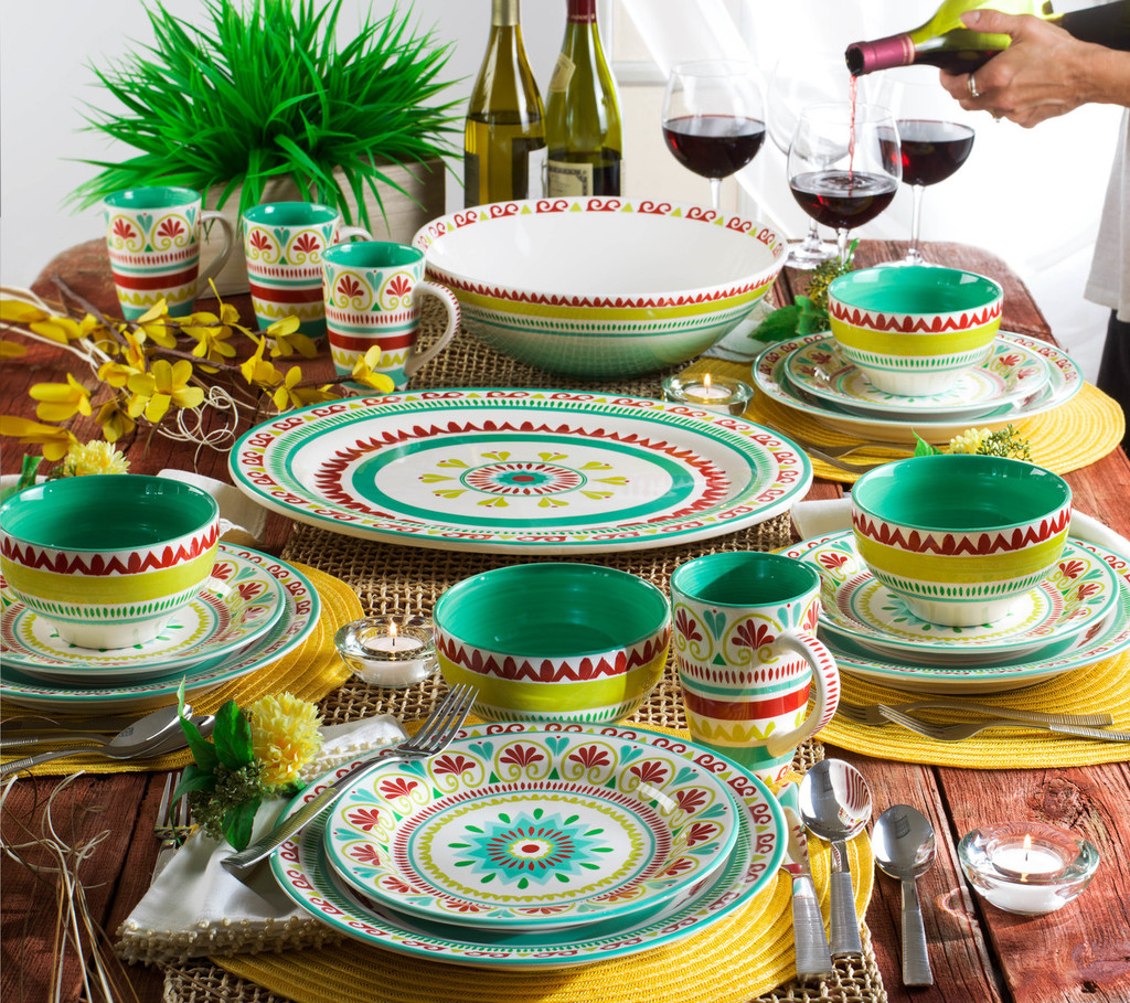 lifestyle shot featuring an oval platter featuring a multicolor design of greens, yellows and reds in the middle of the table with the matching dinnerware laid around. in the back a waiter serves wine. the table is set with yellow place mats, silverware and a large green fern