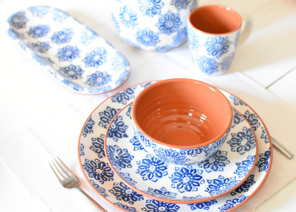 angled shot of various pieces of terra cotta dinnerware with a blue flower design laid on a white table