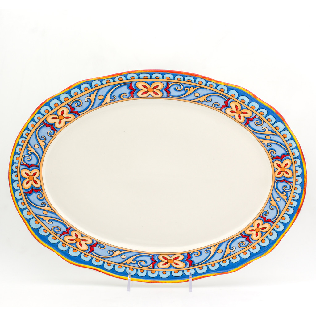 an ornately decorated oval platter with a scalloped lip and a gold and turquoise floral design