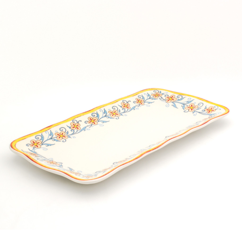 angled view of An ornately decorated rectangular platter with a scalloped edges and a gold and turquoise floral design