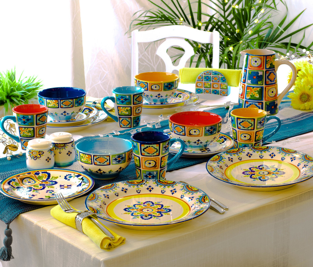 a table featuring a complete dinnerware set with a colorful decal design and several accessory pieces