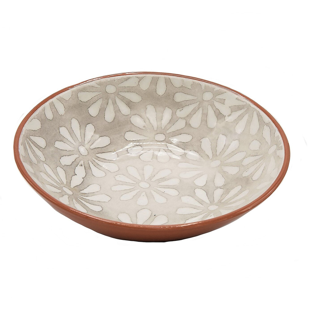 interior of a single shallow bowl with grey and white flowers and a terra cotta exterior