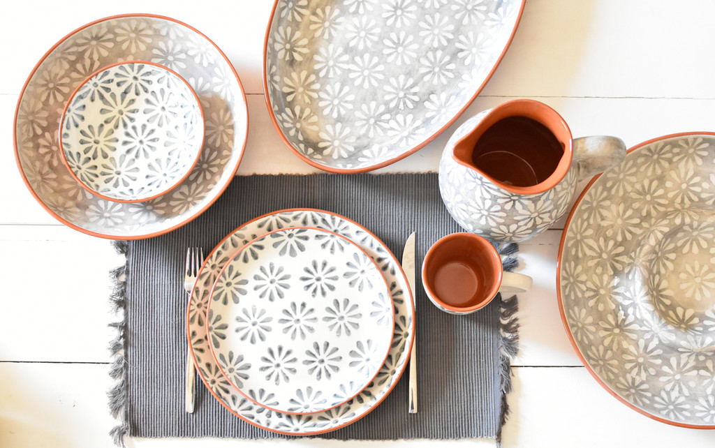 an assortment of dinnerware with grey and white flower patterns and terra cotta bodies set on a white table with a grey place mat