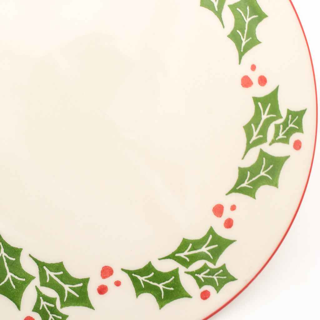 detail view of a cake plate with a holly and berry design