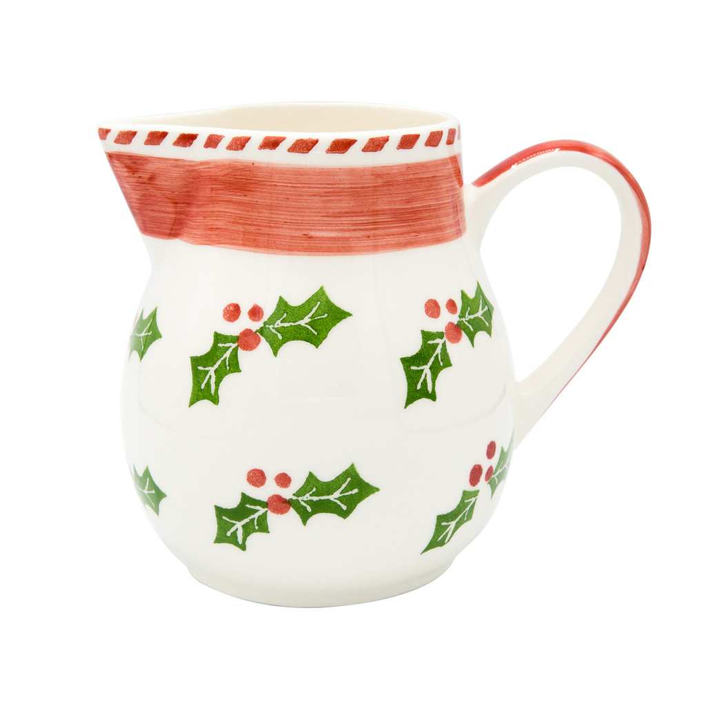 a round pitcher featuring a holly and berry design, a large red stripe, and a red handle