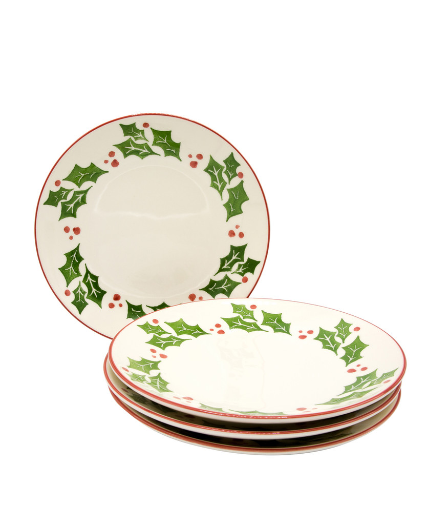 a stack of three dinner plates with a holly and berry design while a fourth plate stands behind the stack