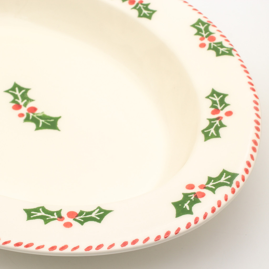 detail view of oval platter with rim and holly and berry pattern