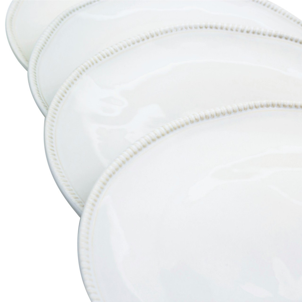 detail view of four white dinner plates showing the beaded detail around the rim and thickness of the plates
