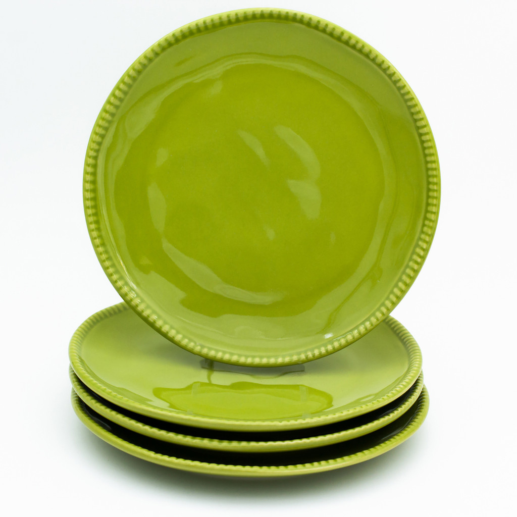 Four green salad plates with beaded detail around the rim. three are stacked and the fourth sits upright on top of the stack
