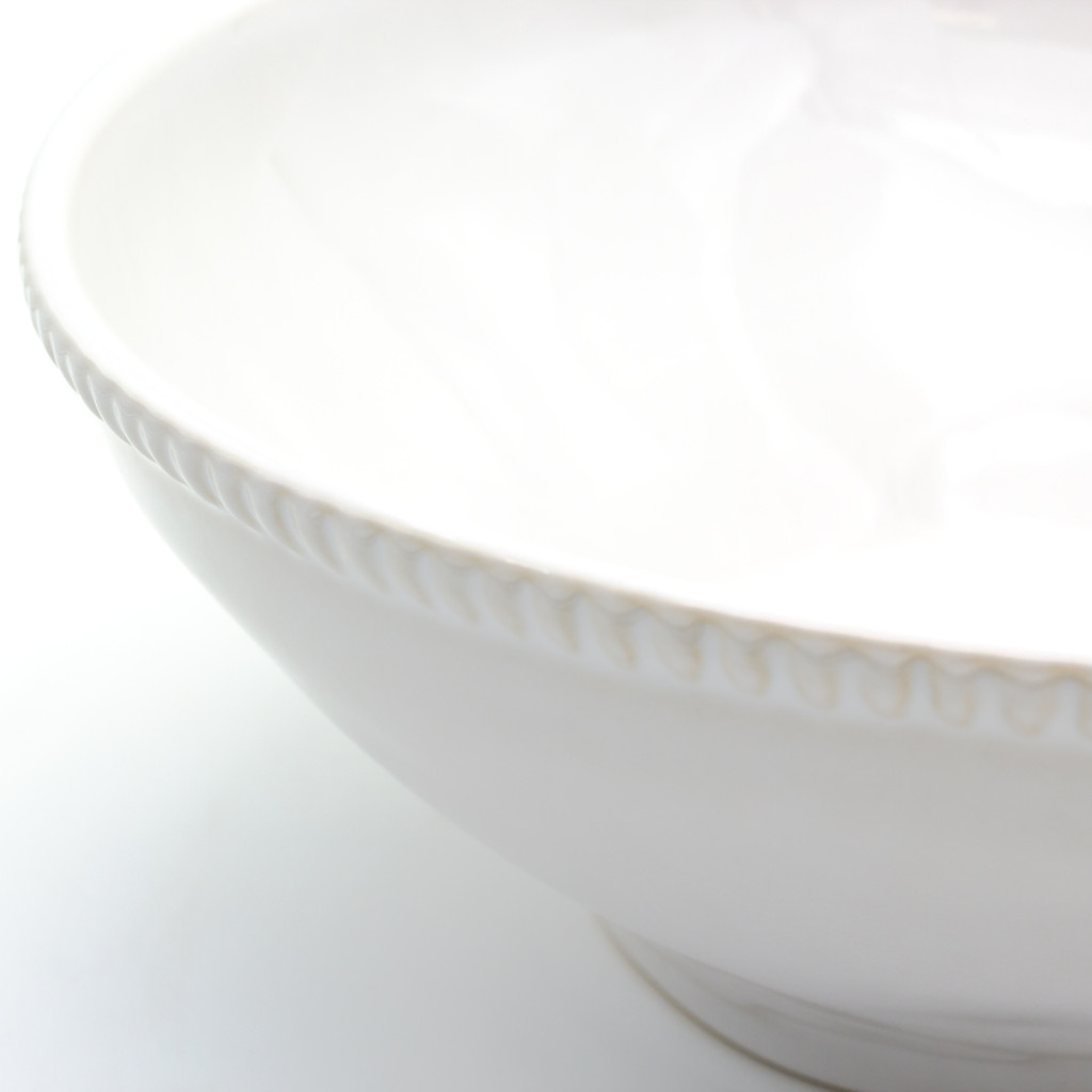 detail view of a large white serving bowl with beaded accents around the rim