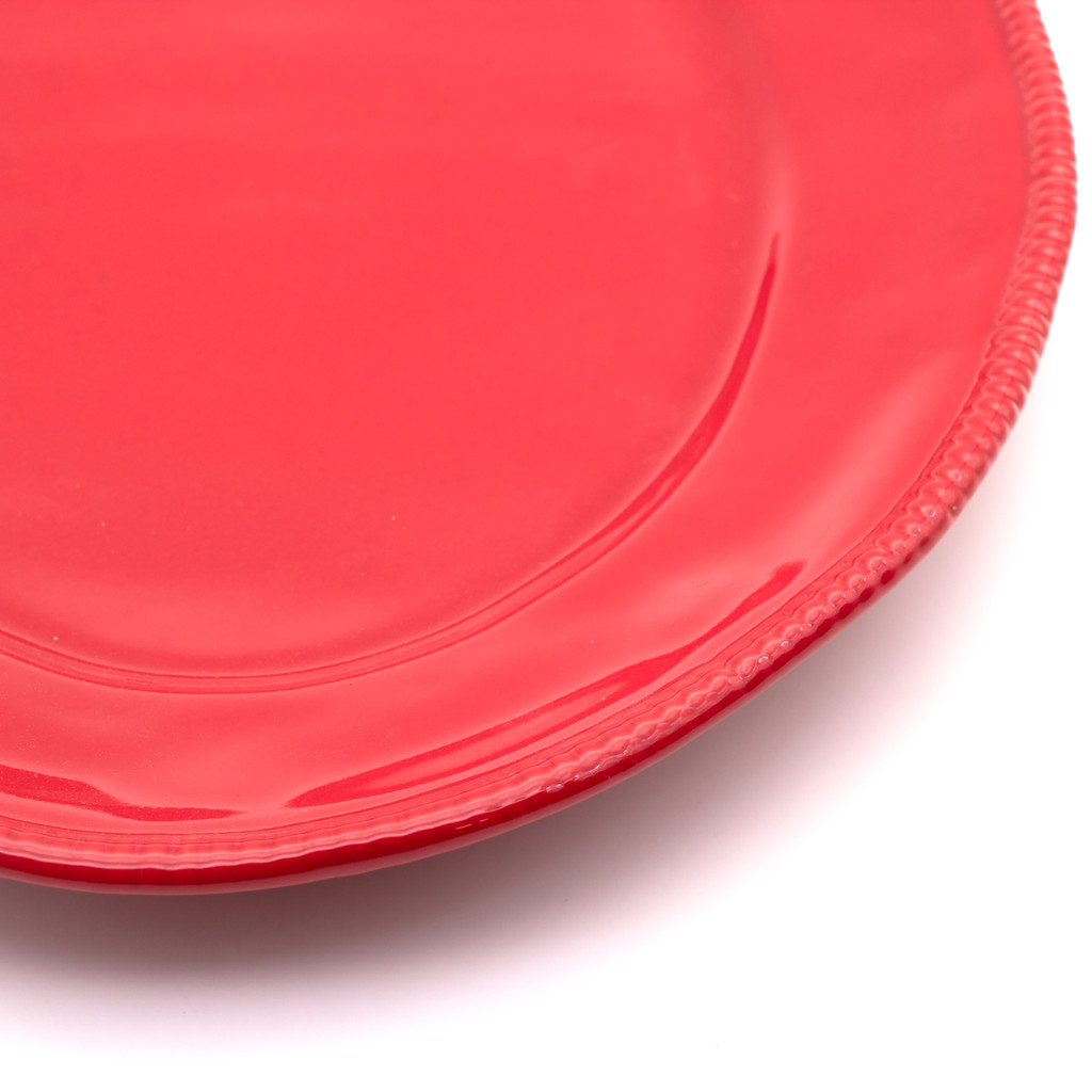 detail view of a red oval platter with beaded accents around the rim