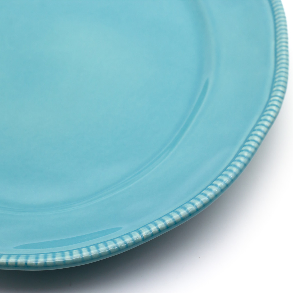 detail view of a blue oval platter with beaded accents around the rim
