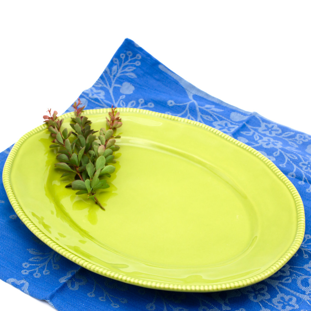 green oval platter with beaded accents around the rim with several herb sprigs resting on it and a blue cotton place mat underneath