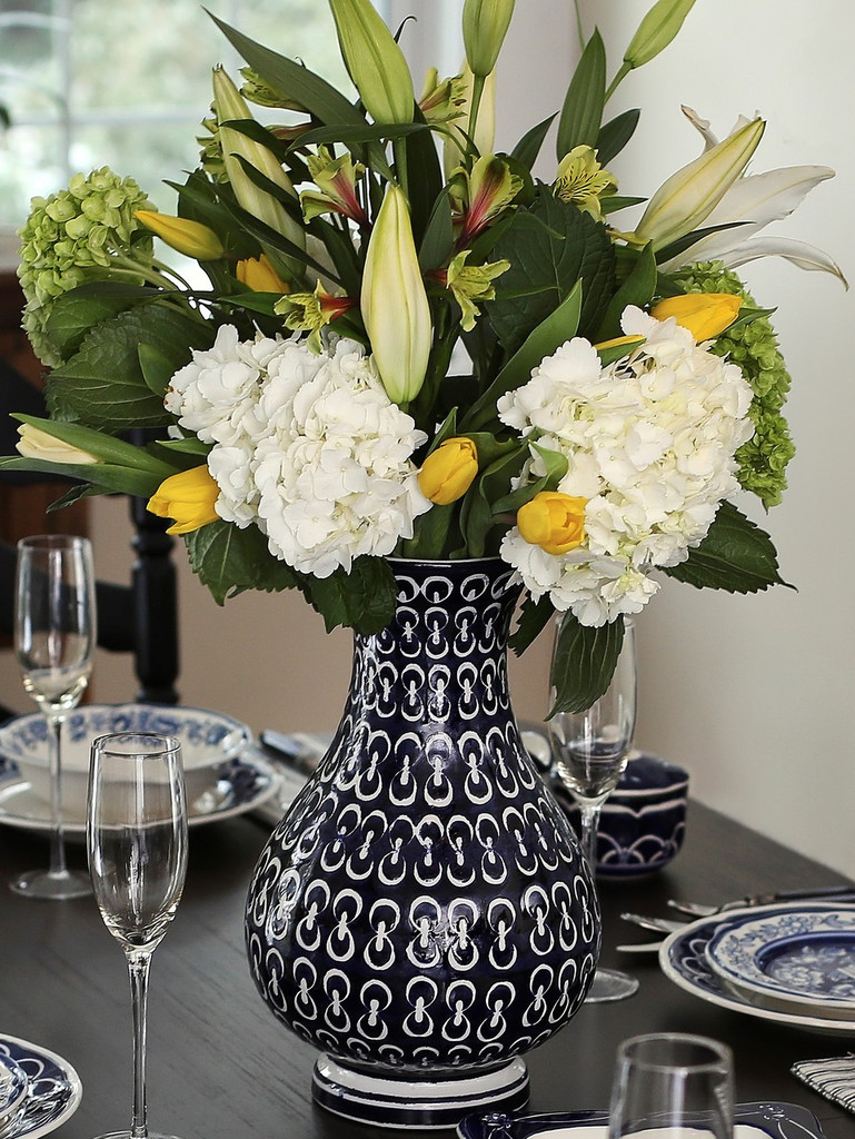 Alternate shot Lifestyle of Round and curvy vase with wide lip and blue-and-white hand-painted chain design featuring large hydrangea blooms and lily buds in the vase. set on a formal dinning table