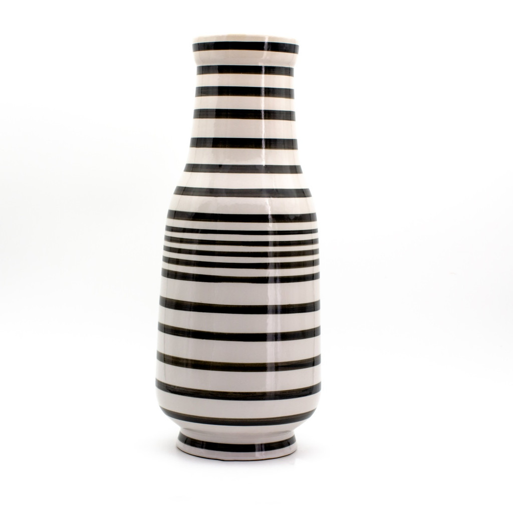 A tall and squarish white and black vase with hand-painted stripe design