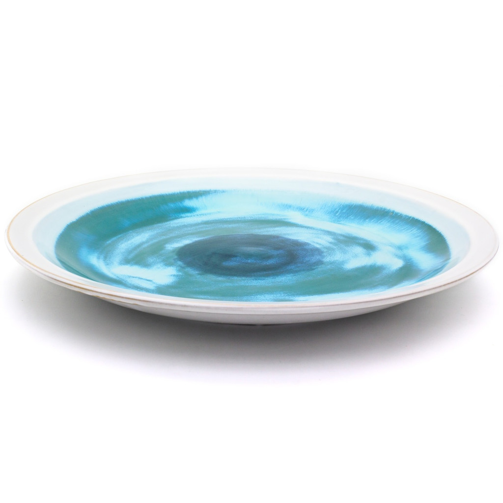 Side view of A large decorative plate with a wide white rim and swirled blue center featuring sky blue, turquoise, sea green, and royal blue shades.