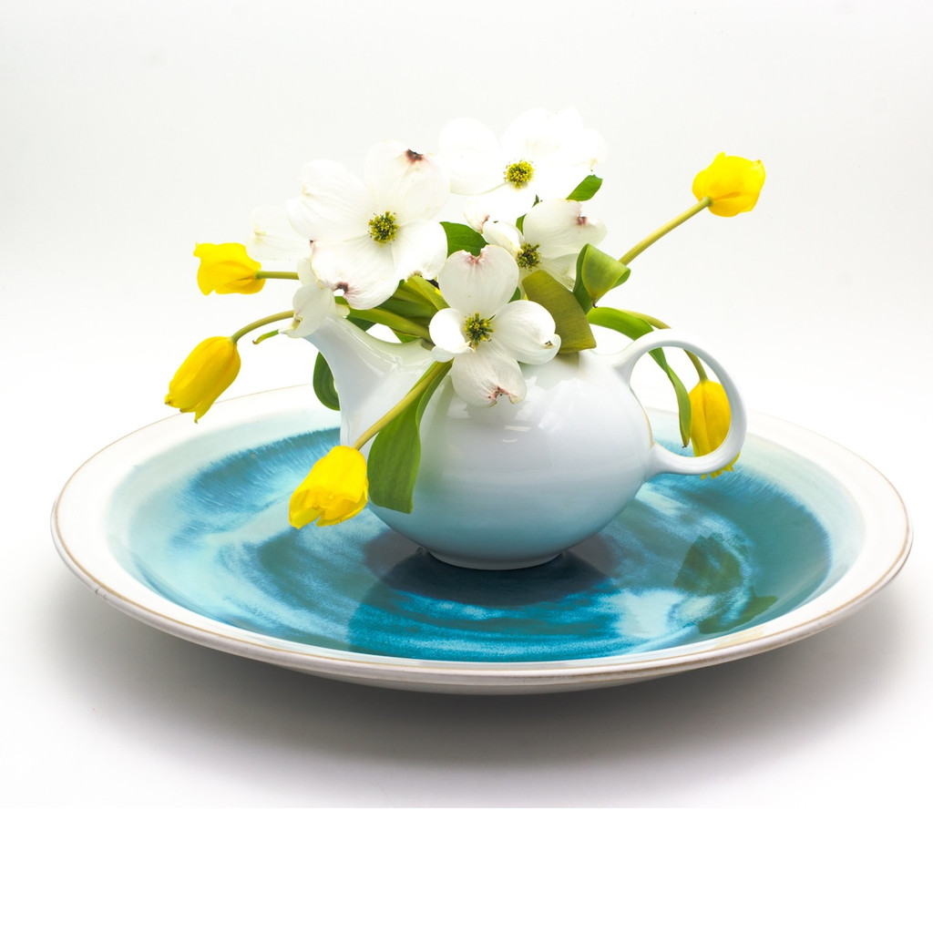 Lifestyle shot of A large decorative plate with a wide white rim and swirled blue center featuring sky blue, turquoise, sea green, and royal blue shades featuring a white teapot filled with a floral arrangement of tulips and dogwood resting on the center of the plate.