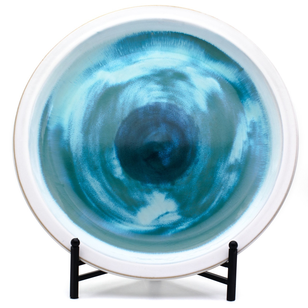 A large decorative plate with a wide white rim and swirled blue center featuring sky blue, turquoise, sea green, and royal blue shades. Propped on a black stand (included).