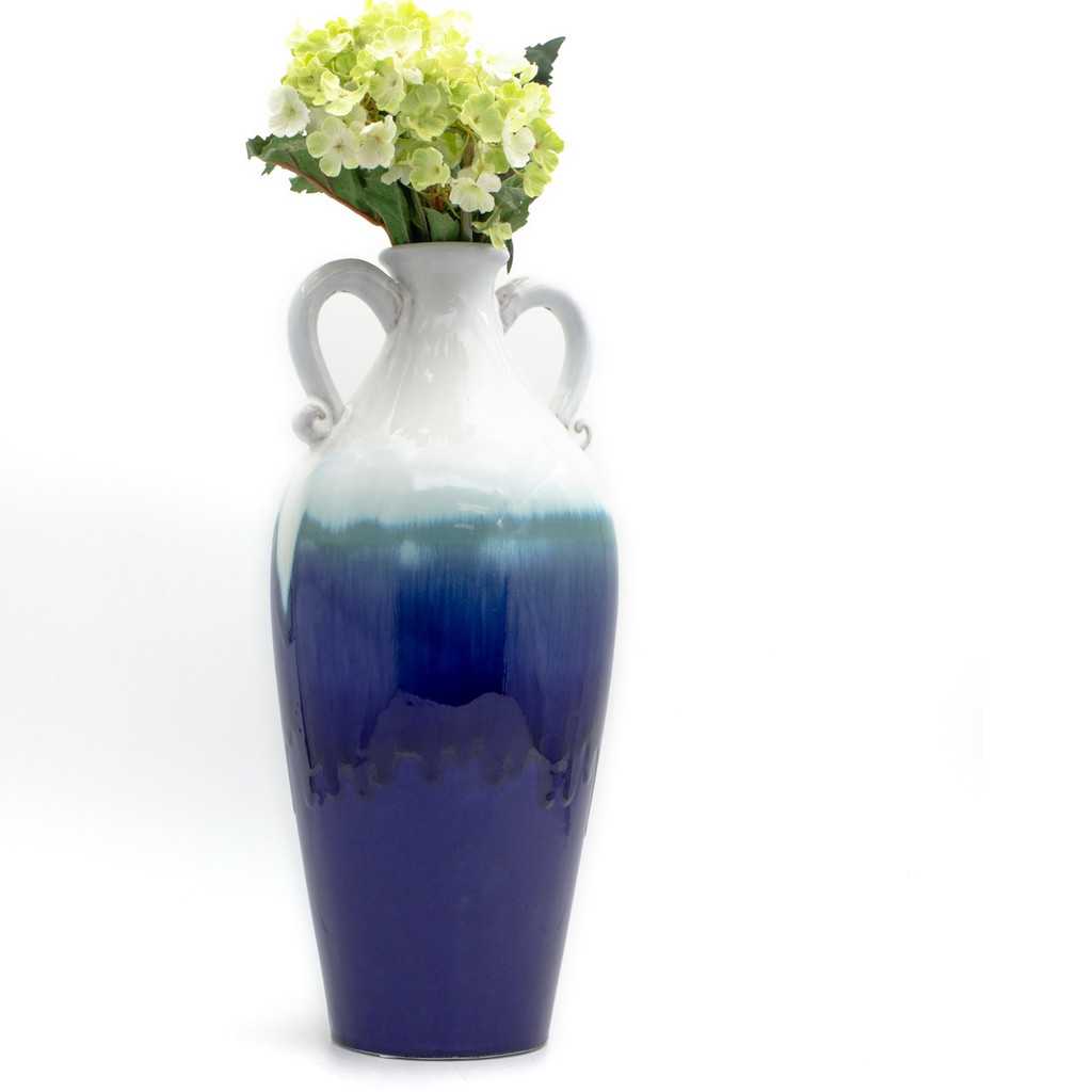 Lifestyle of Side view of A two-handled amphora vase with a white top and white handles. the bottom two thirds of the vase are deep blue with a turquoise band of dripped glaze just below the handles. Featuring a small bouquet of artificial yellow flowers in the vase.