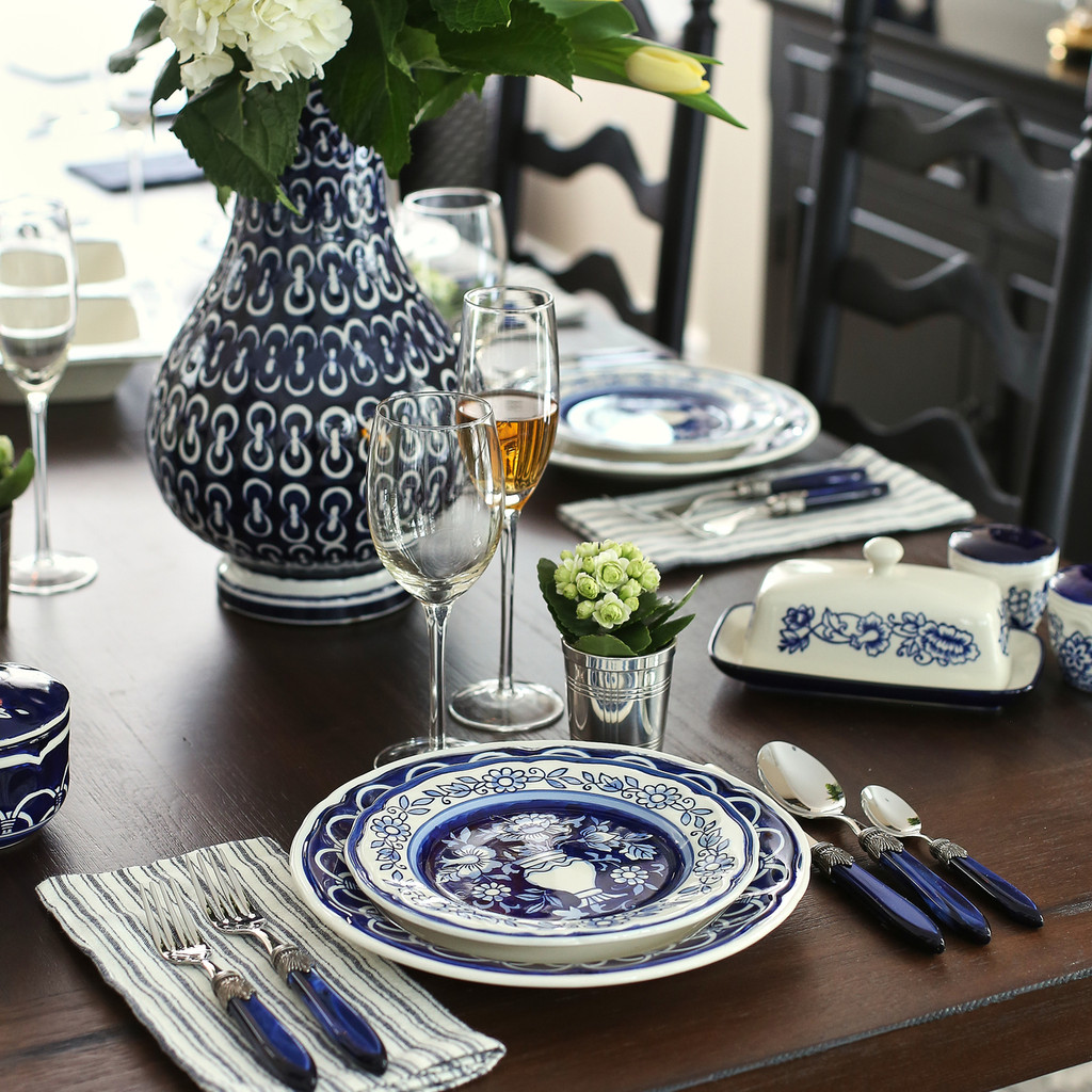 a salad plate and dinner plate hand-painted with a blue floral design on a formal dining table. in the background a blue vase with a chain pattern and more pieces of the same dinnerware
