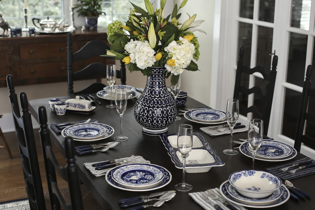a formal table set with blue hand-painted floral dinnerware and a central blue vase filled with a large bouquet
