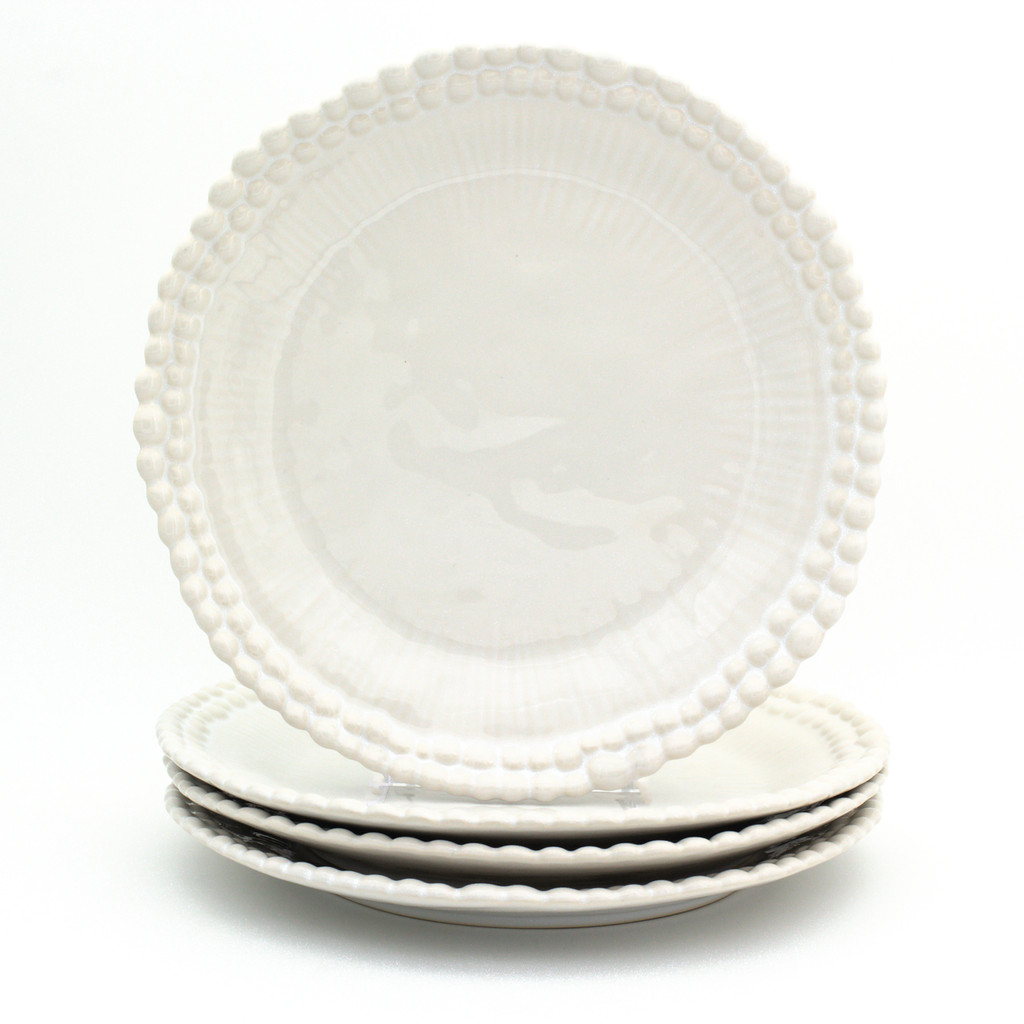 stack of three white dinner plates with two rings of beads around the rim, a fourth plate standing on the stack