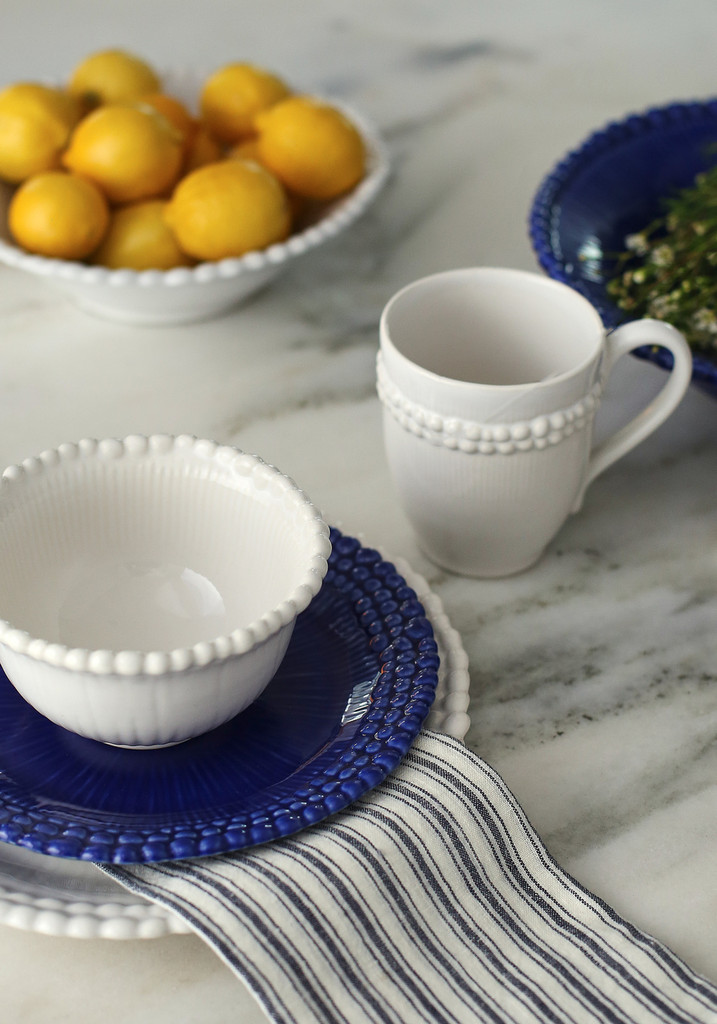 lifestyle of a beaded rim dinnerware set in mixed blue and white accented with lemons and a striped napkin