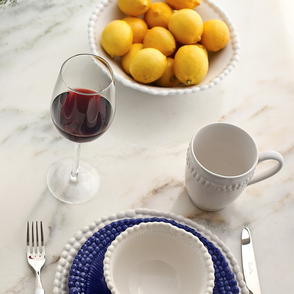 lifestyle of wide lipped white bowl with beaded rim filled with lemons