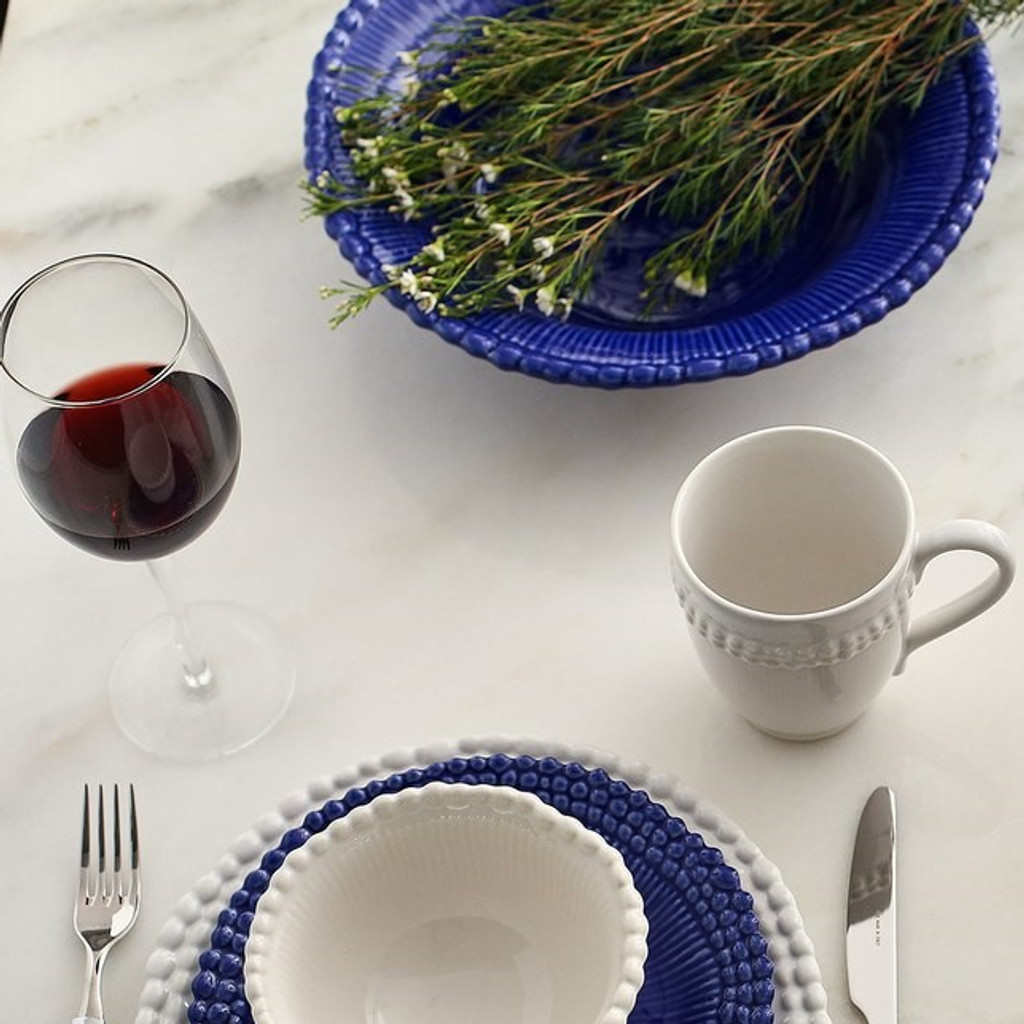 lifestyle of a beaded rim dinnerware set in mixed blue and white accented with rosemary