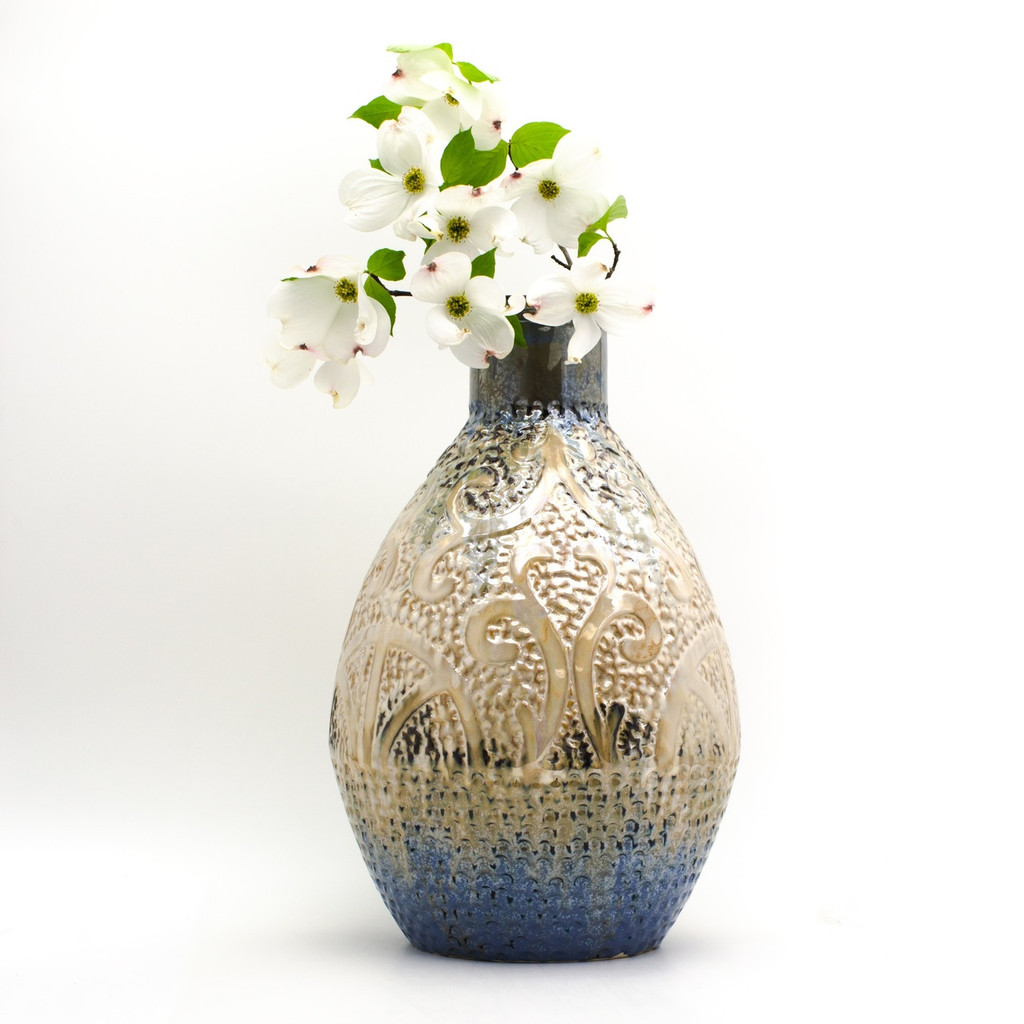 Lifestyle view of A shiny somewhat metallic vase with a coppery top, brown body, and deep blueish green bottom. The vase features engraved and embossed abstract details that resemble seaweed and a ship wheel and is marked all over with small indents like scales. The vase has a branch of dogwood in it.