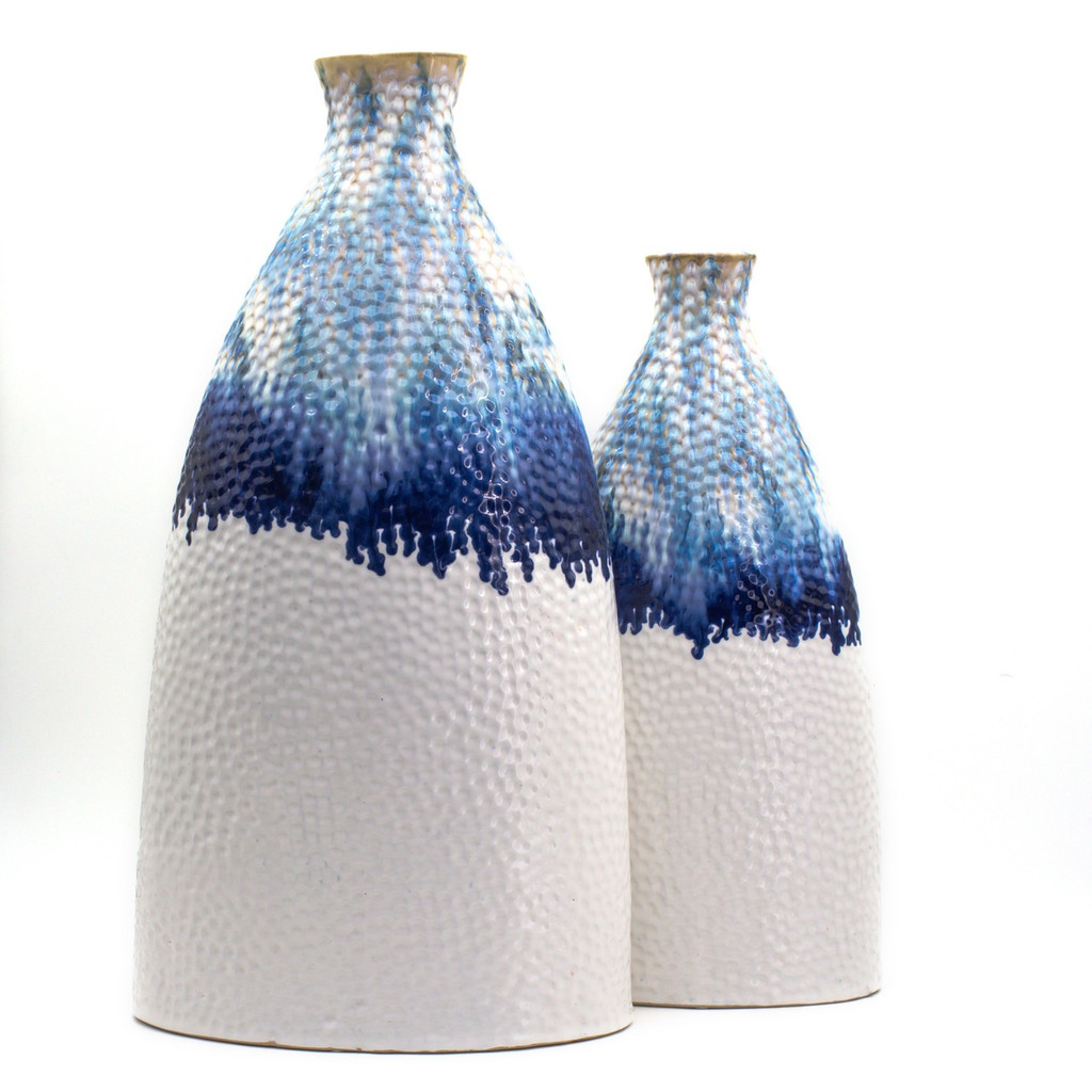 Comparison view of a flattened shoulder vase. The vase features shades of blue glaze dripping from the top that transition to a flat white. The vase is marked all over with small indents like sand that has been brushed by the tide. The photo shows the larger version of the vase side-by-side to the smaller version.