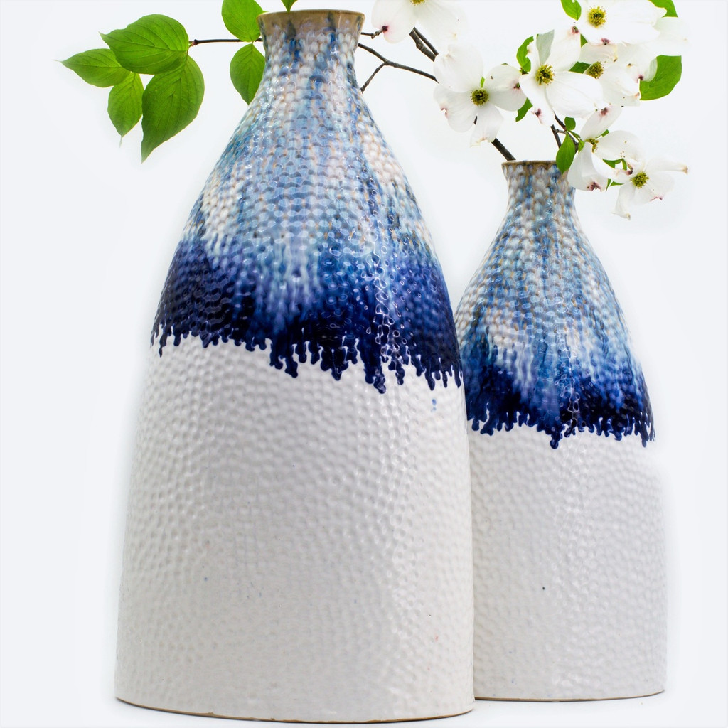 Lifestyle view of a flattened shoulder vase. The vase features shades of blue glaze dripping from the top that transition to a flat white. The vase is marked all over with small indents like sand that has been brushed by the tide. Compares the large vase to the small vase side-by-side. The smaller vase has a large dogwood branch in it.