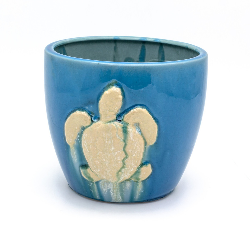 Turquoise planter with a turtle painted in a dripping white glaze.