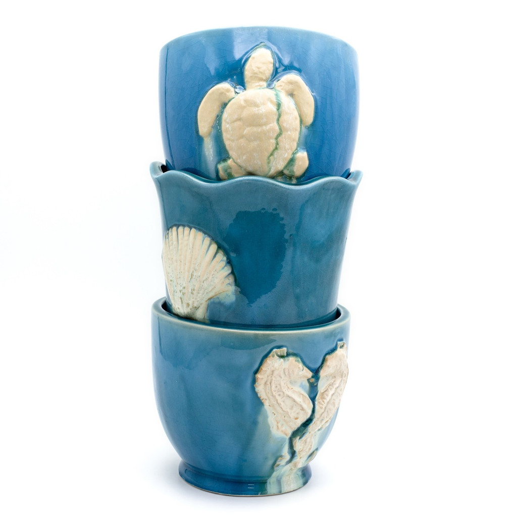 Stack of three planters showing the turtle on the top. The middle planter features a shell, and the bottom features two seahorses