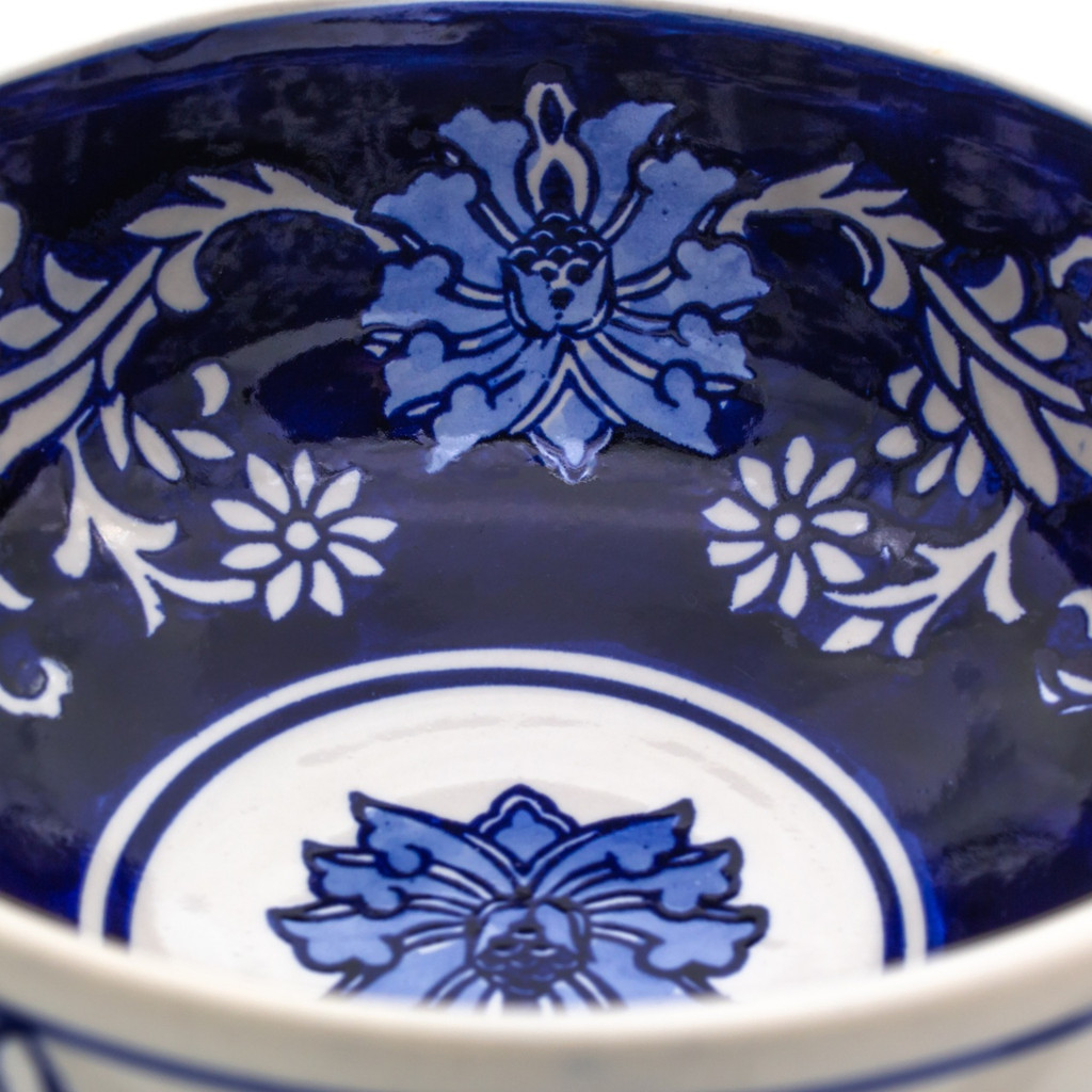 detail view of a small footed bowl with white exterior and dark blue interior decorated with a hand-painted lotus design showing primarily the interior and the detail of the brushwork