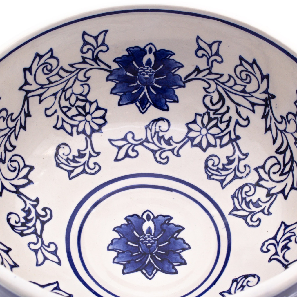 Detail view of a small footed bowl with dark blue exterior and white interior decorated with a hand-painted lotus design showing primarily the interior and the detail of the brushwork