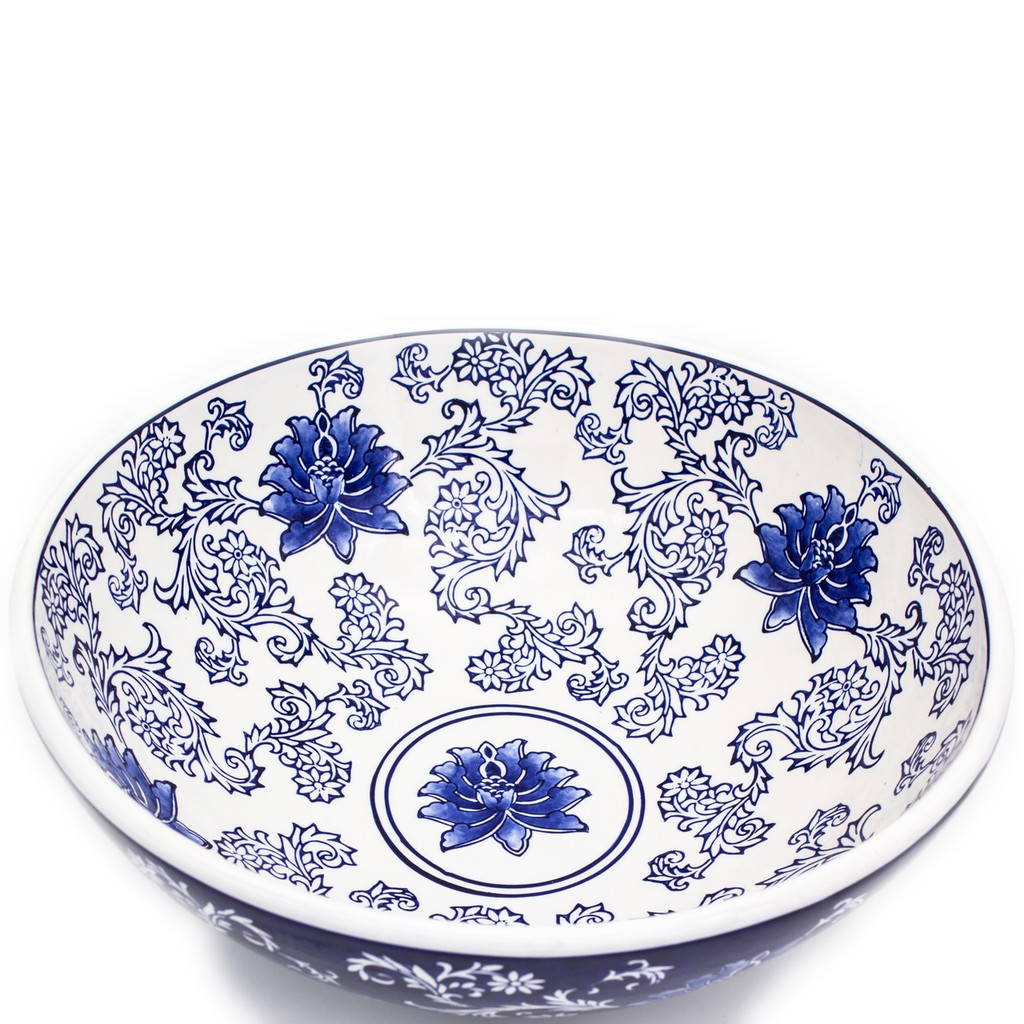angled shot of a large wide bowl with dark blue exterior and white interior decorated with a hand-painted lotus design showing the pattern of the interior