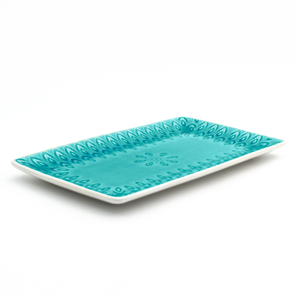 side view of lagoon rectangular platter with crackle glaze and an embossed peacock feather design