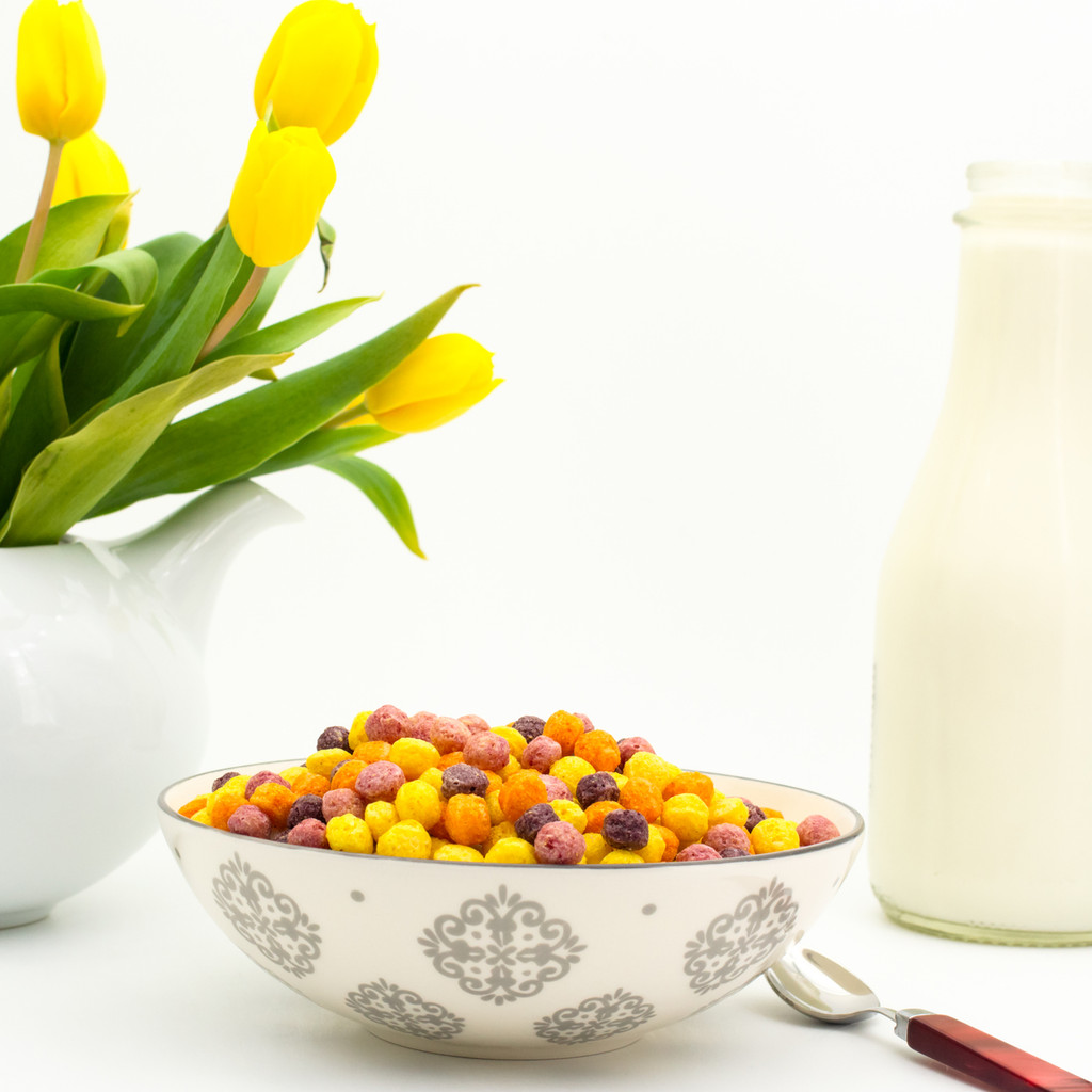 in the background a white teapot contains a bouquet of yellow tulips next to a glass bottle of milk