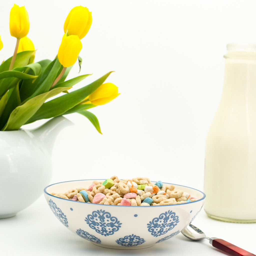 single white bowl with blue patterns filled with cereal. in the background a white teapot contains a bouquet of yellow tulips next to a glass bottle of milk