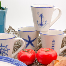lifestyle of four white cups with assorted blue nautical designs and blue rims. the cups feature a lighthouse, a ships wheel, a starfish, and an anchor. two tomatoes side in front of the cups and the edges of the ahoy salad plates and seashell planter show at the edges
