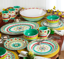 lifestyle featuring a short wide serving bowl featuring a multicolor design of greens, yellows and reds in the back center of a table laid with matching dinnerware and oval platter. the table is set with yellow place mats, silverware, and decorated with fall foliage