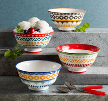lifestyle of four bowls with assorted colors and geometric patterns. the bowls are set on stone steps and one contains ice cream