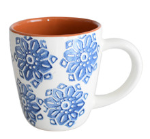 a single mug with blue flowers on the outside and terra cotta on the inside and white handle