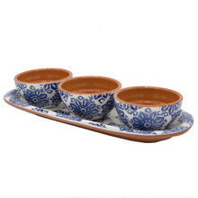 three dipping bowls with blue flowers on the outside and terra cotta on the inside sit on a small tray decorated with blue flowers