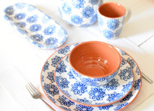 various pieces of terra cotta dinnerware with a blue flower design laid on a white table