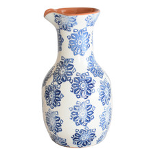 a wine carafe with a blue floral design and terra cotta interior