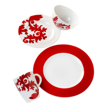 four pieces of red and white dinnerware featuring a damask design